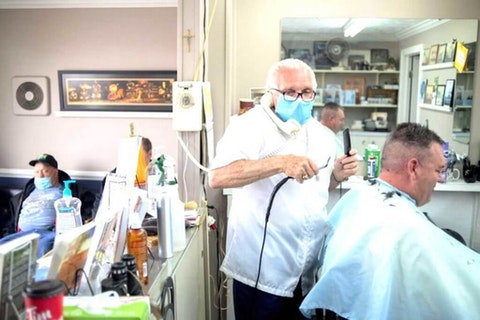 Karl Manke, 77, left, wears a mask while cutting hair, Tuesday, May 5, 2020 at Karl Manke's Barber and Beauty Shop in Owosso, Mich. Manke re-opened his doors on Monday in defiance of Gov. Gretchen Whitmer's executive order mandating salons, barbershops and other businesses to stay closed. He has already given nearly 100 haircuts, and fields more calls than that daily, all while continuing to cut hair. (Jake May/The Flint Journal via AP)
