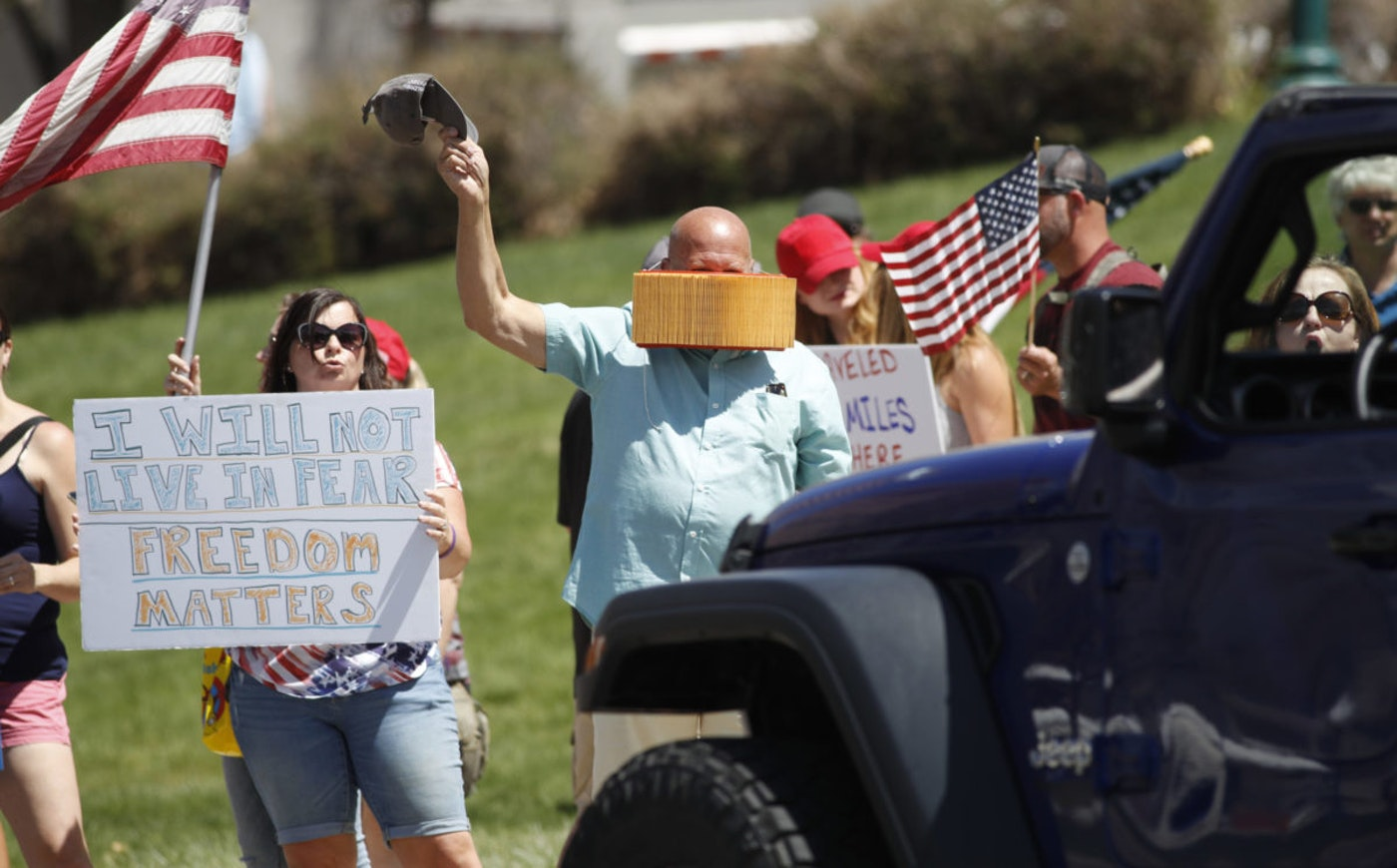 Protesters call for the reopening of Colorado while restrictions put in place to stop the spread of the new coronavirus were eased in most of the state, Friday, May 1, 2020, in front of the State Capitol in Denver. (AP Photo/David Zalubowski)