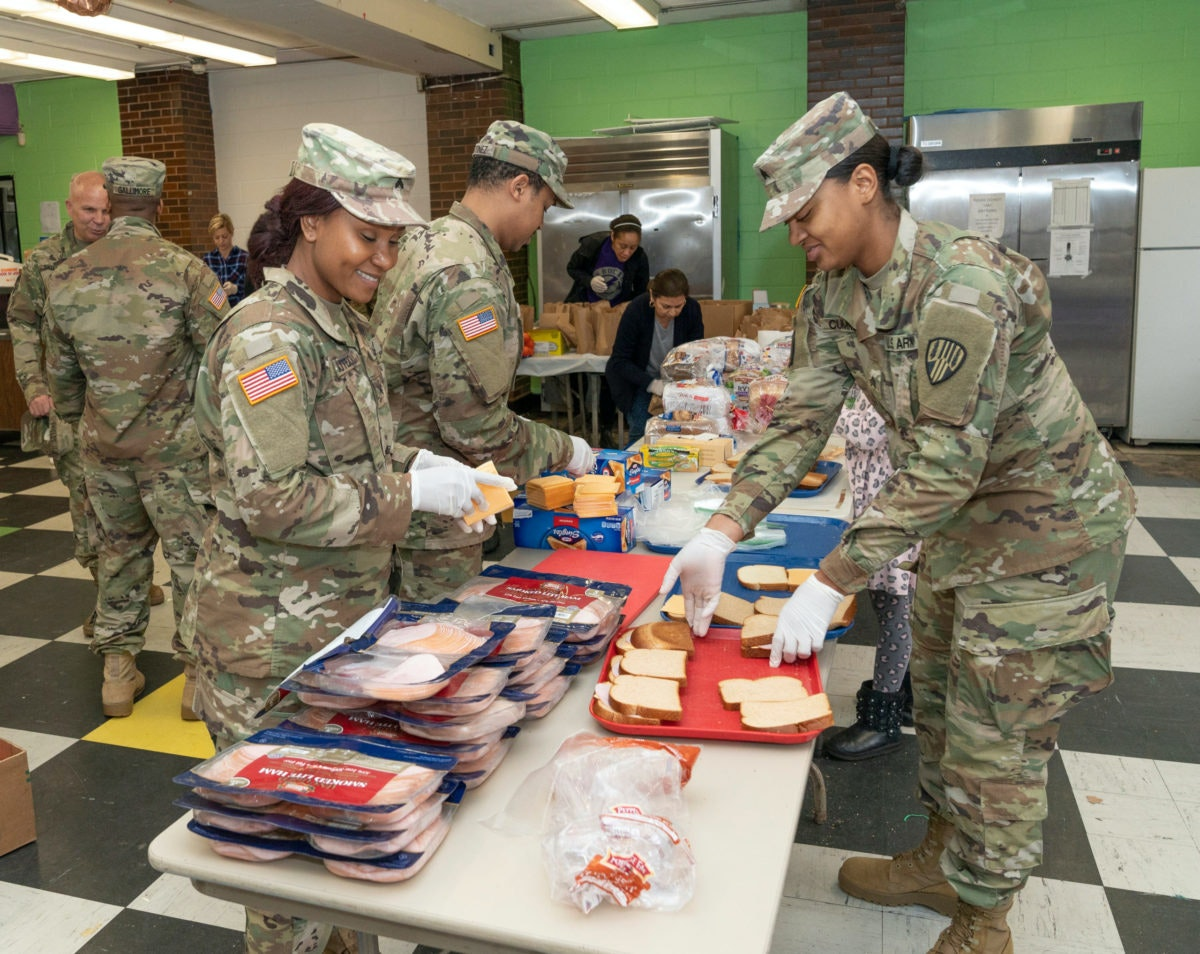 Members of National Guard & volunteers prepare bags of food to residents near a one-mile radius containment area set up to halt spread of COVID-19 in New York. Image via Shutterstock