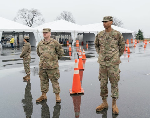 Members of the National Guard guarding newly opened drive through COVID-19 mobile testing center organized by Northwell hospital at Glen Island Park. Image via Shutterstock