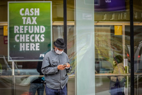 A man wearing a face mask due to COVID-19 leaves a check cashing service center, Friday Friday April 3, 2020, in the East Flatbush area of New York. (AP Photo/Bebeto Matthews)