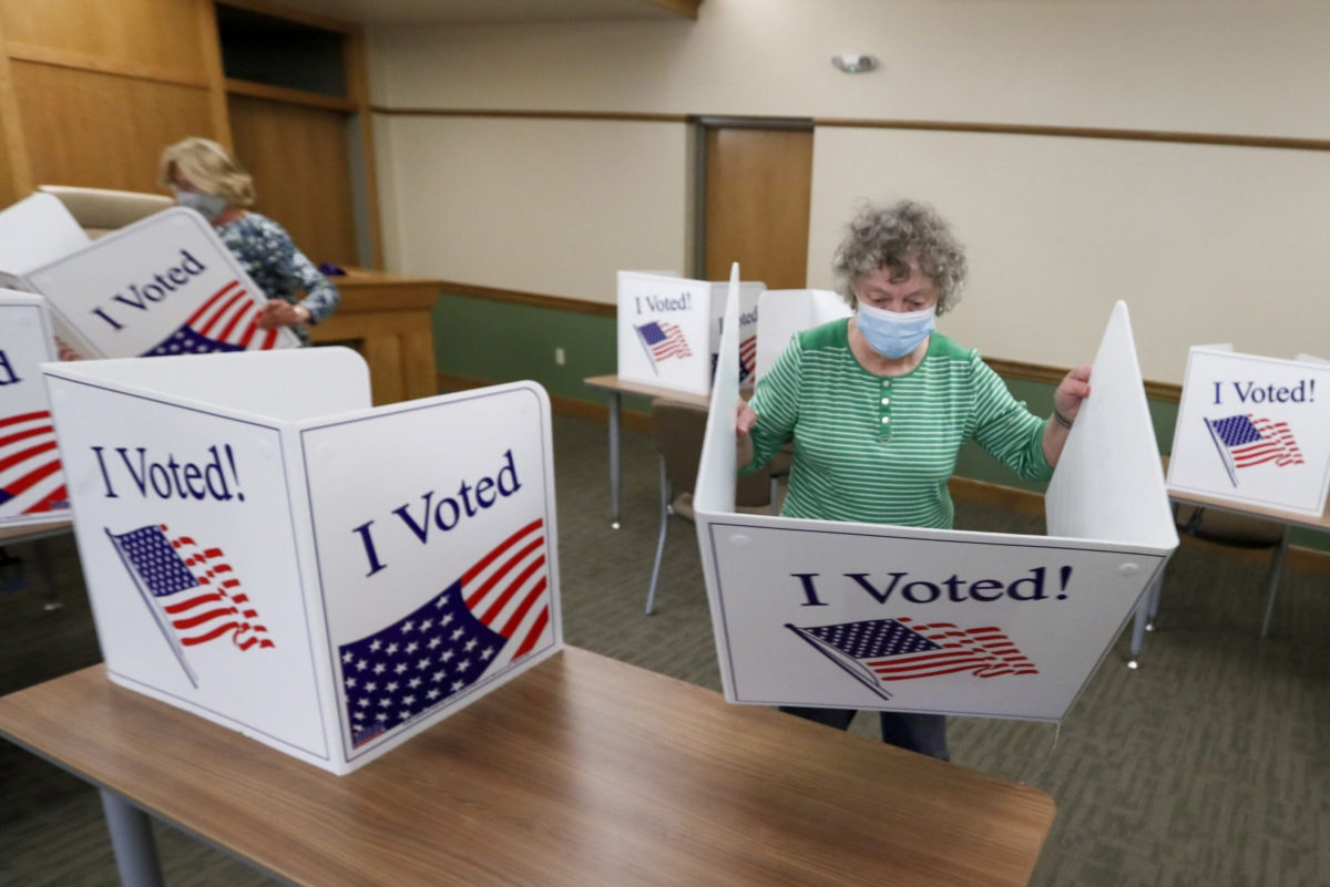 Marty Goetz, right, and Diane White, prepare the voting screens as they start to set up a polling place Monday, June 1, 2020, for the voting for Tuesday's Pennsylvania primary in Jackson Township near Zelienople, Pa. (AP Photo/Keith Srakocic)