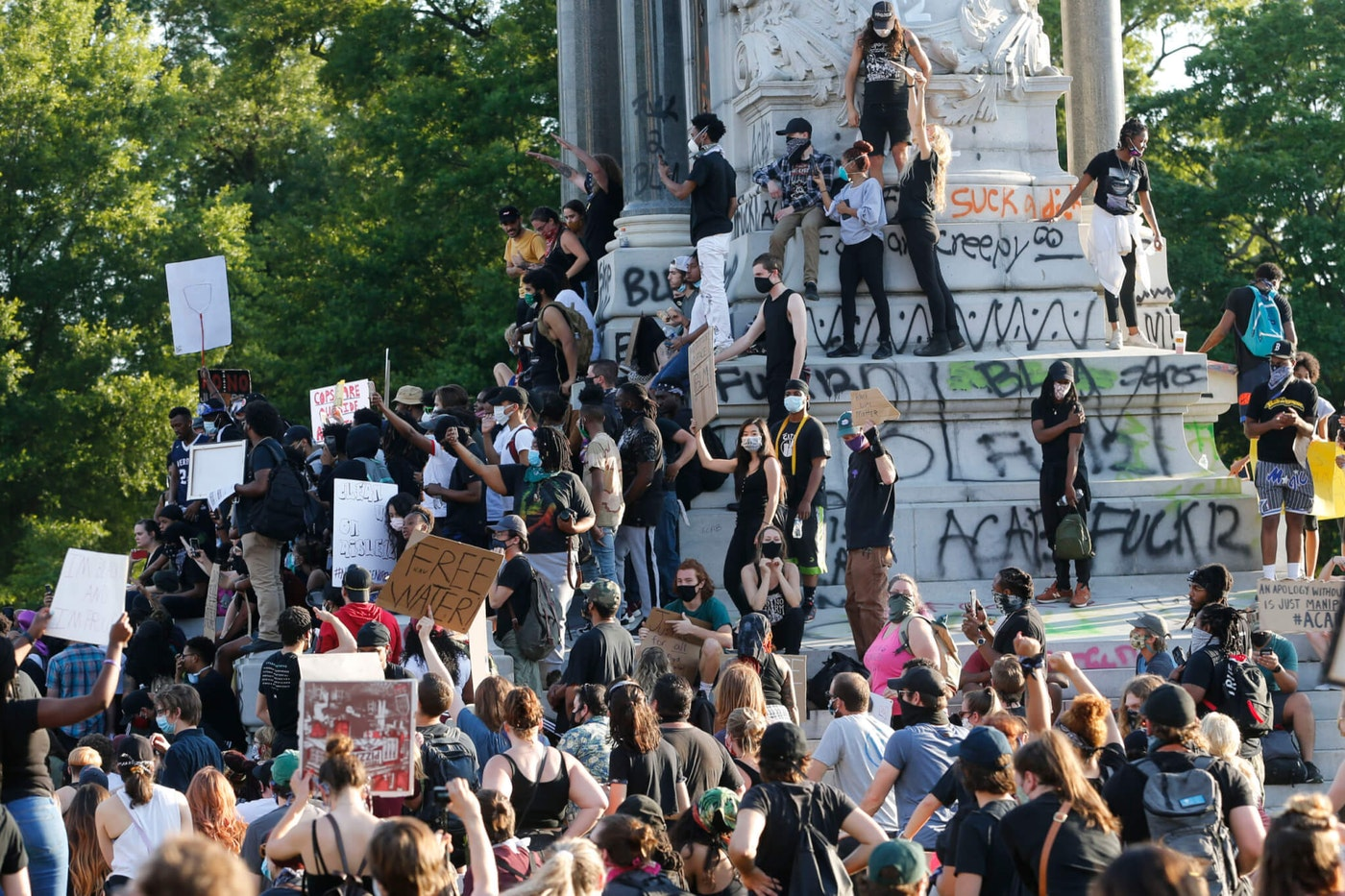 This Tuesday, June 2, 2020 file photo shows a large group of protesters gather around the statue of Confederate General Robert E. Lee on Monument Avenue near downtown in Richmond, Va. . (AP Photo/Steve Helber, File)