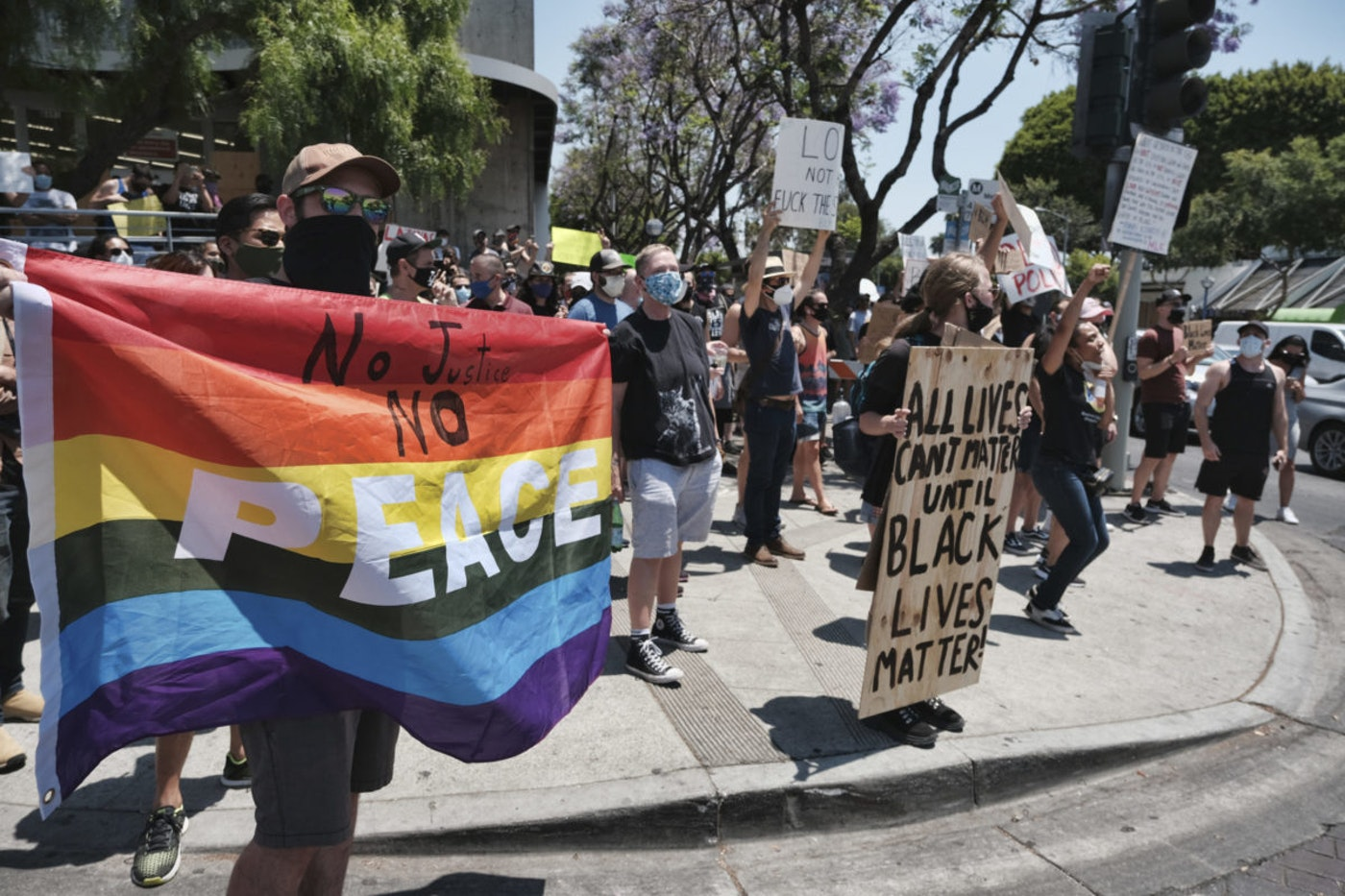 LGBTQ community members join in support with Black Lives Matter protesters holding signs and chanting slogans on an intersection in West Hollywood, Calif. on Wednesday, June 3, 2020, over the death of George Floyd, a black man who was in police custody in Minneapolis. Floyd died after being restrained by Minneapolis police officers on Memorial Day. (AP Photo/Richard Vogel)