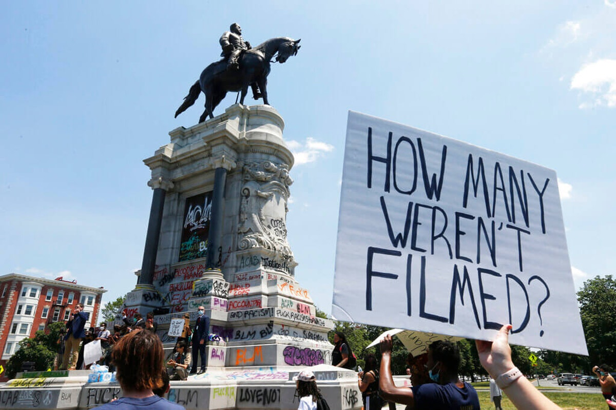 """Rev. Robert W. Lee, IV, left, the fourth great nephew of Confederate General Robert E. Lee, speaks to protesters at the foot of the statue of Confederate General Robert E. Lee on Monument Avenue Thursday, June 4, 2020, in Richmond, Va. Lee supports the removal of the statue, which Gov. Ralph Northam said will be removed """"as soon as possible"""" from Monument Avenue. (AP Photo/Steve Helber)"""
