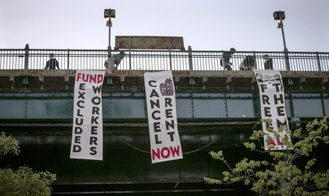 In this May 21, 2020, file photo, people from a support organization for immigrant and working class communities unfold banners, including one advocating rent cancelation, on a subway platform in the Queens borough of New York during a vigil memorializing people who died from coronavirus.  (AP Photo/Bebeto Matthews, File)