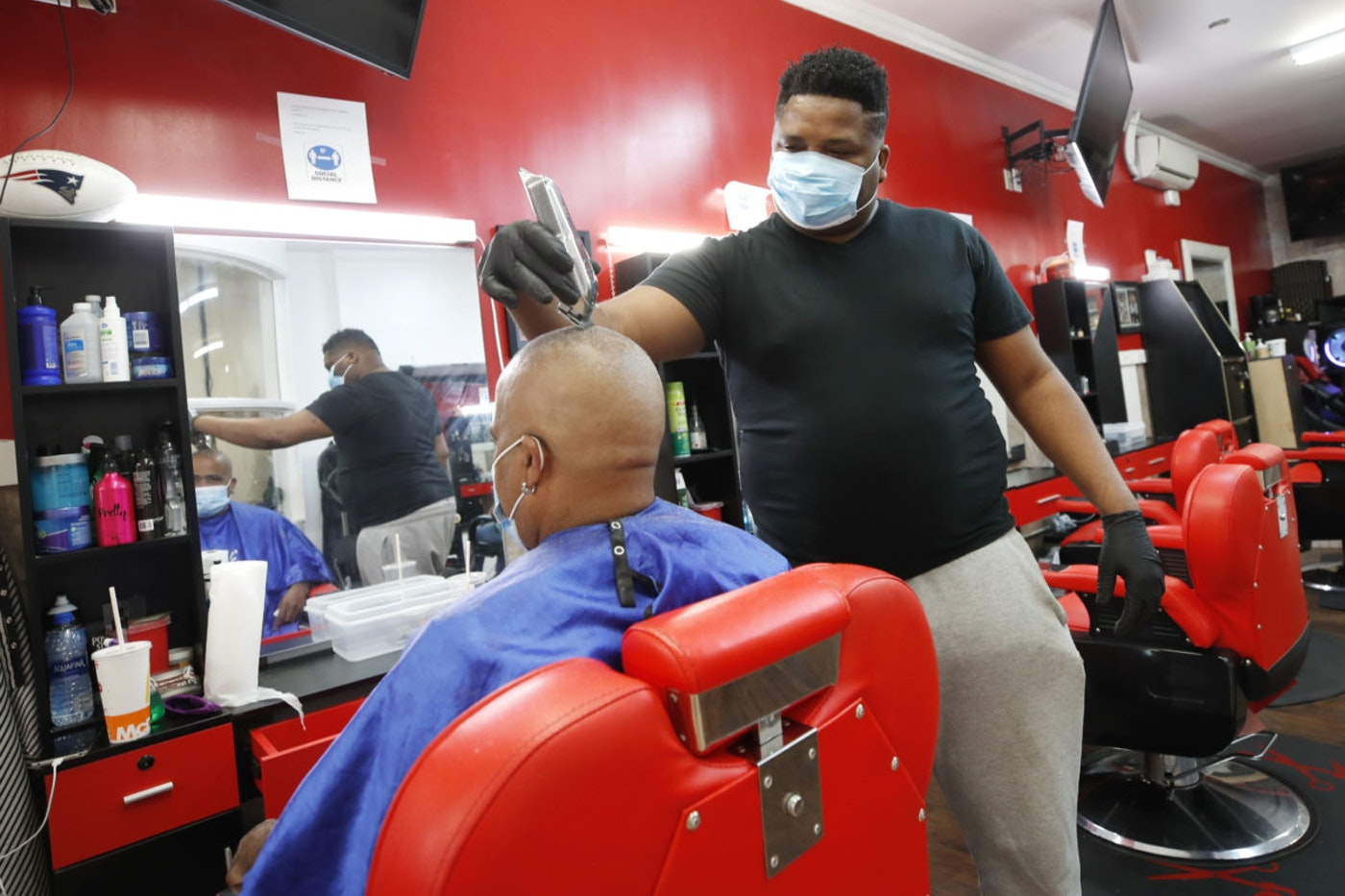 Wilkin Soto works on a customer at the Castillo Barbershop, Friday, June 5, 2020, in Lawrence, Mass. The U.S. unemployment rate fell unexpectedly in May to 13.3% — still on par with what the nation witnessed during the Great Depression — as states loosened their coronavirus lockdowns and businesses began recalling workers. (AP Photo/Elise Amendola)
