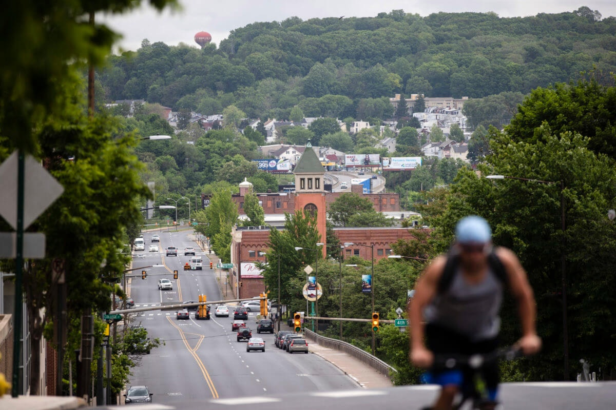 A cyclist pedals up a hill in Allentown, Pa., Friday, May 29, 2020. Allentown predicts a budget deficit of over $10 million, a number officials say could go higher if the economy doesn't rebound quickly. (AP Photo/Matt Rourke)