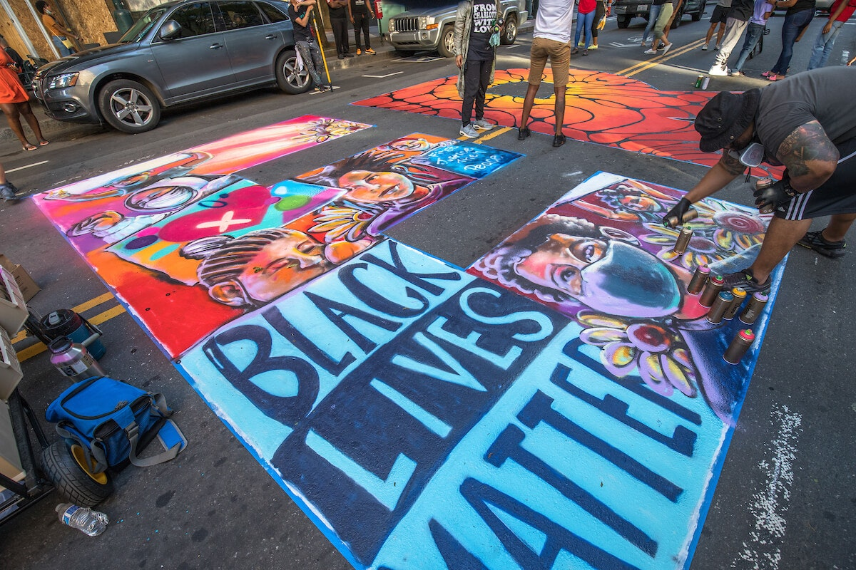 "Artist John Hairston was one of 16 artists painting a letter in the phrase ""Black Lives Matter"" on Tryon Street in uptown Charlotte. (Cardinal & Pine photo by Grant Baldwin)."