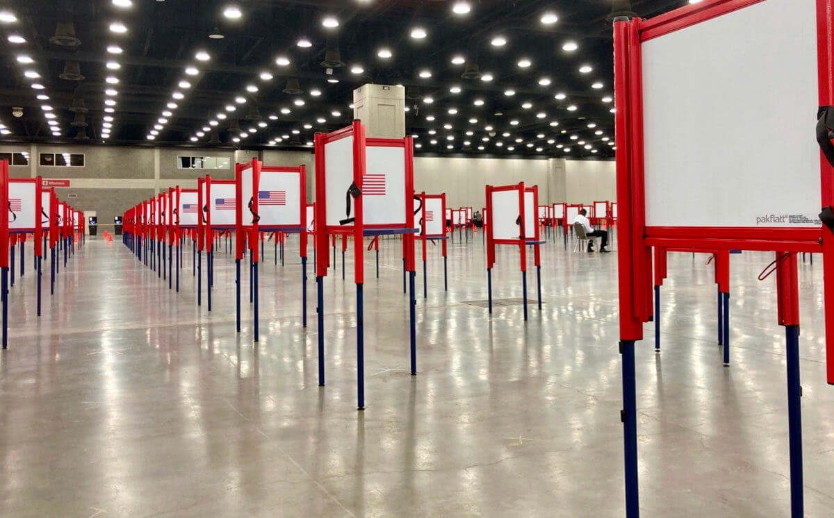 Voting stations are set up for the primary election at the Kentucky Exposition Center, Monday, June 22, 2020, in Louisville, Ky. With one polling place designated for Louisville on Tuesday, voters who didn't cast mail-in ballots could potentially face long lines in Kentucky's unprecedented primary election.  (AP Photo/Piper Blackburn)