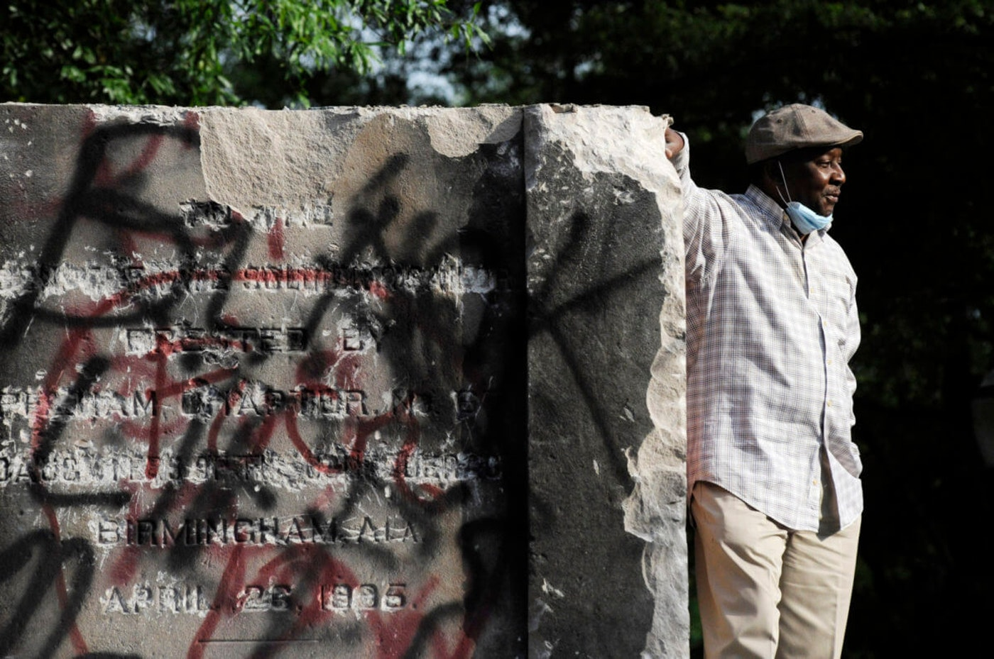 Robert Walker poses for a photograph on the remains of a Confederate memorial that was removed overnight in Birmingham, Ala., on Tuesday, June 2, 2020. (AP Photo/Jay Reeves)