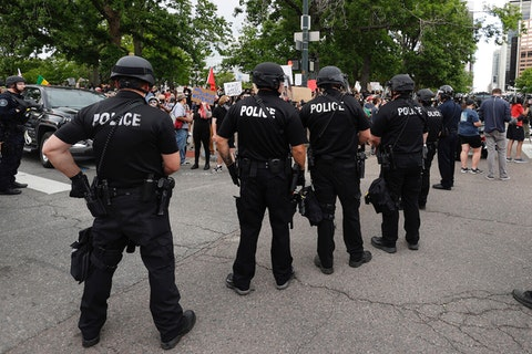 In this May 29, 2020 file photo, Denver Police officers form a line of defense as they square off with participants in a protest over the death of George Floyd, in Denver. (AP Photo/David Zalubowski)