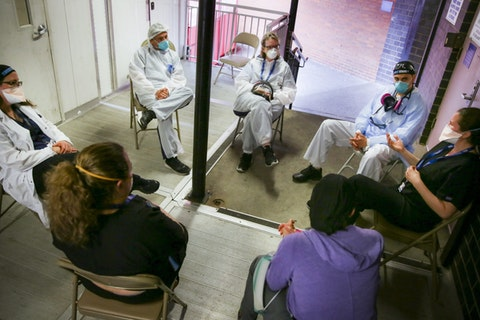 Hospital workers sit for a group counseling session at Elmhurst Hospital to talk about their experiences dealing with the COVID-19 pandemic, Friday, May 29, 2020, in New York. (AP Photo/Robert Bumsted)