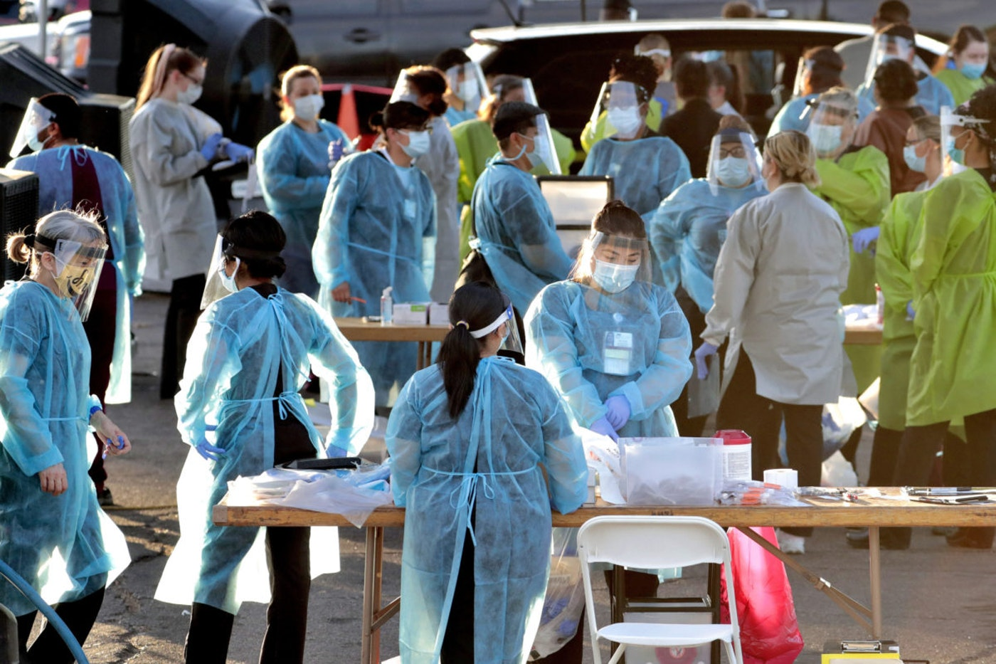 In this photo taken Saturday, June 27, 2020, medical personnel prepare to test hundreds of people lined up in vehicles in Phoenix's western neighborhood of Maryvale in Phoenix for free COVID-19 tests organized by Equality Health Foundation, which focuses on care in underserved communities. (AP Photo/Matt York)