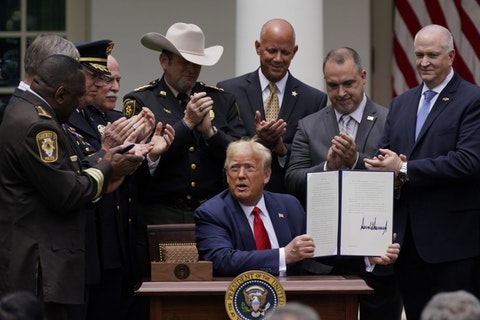 Law enforcement officials applaud after President Donald Trump signed an executive order on police reform, in the Rose Garden of the White House, Tuesday, June 16, 2020, in Washington. (AP Photo/Evan Vucci)