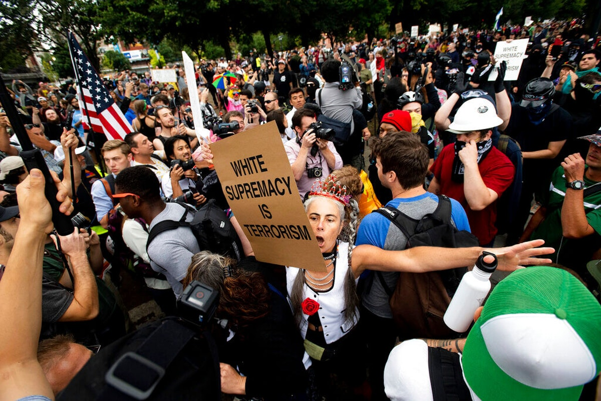 """A counter-protester confronts members of the Proud Boys and other right-wing demonstrators during an """"End Domestic Terrorism"""" rally in Portland, Ore., on Saturday, Aug. 17, 2019. (AP Photo/Noah Berger)"""
