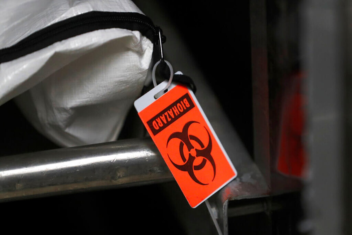 An orange biohazard tag hangs from a body bag in an isolated refrigerated unit set aside for bodies infected with coronavirus at the Cook County morgue in Chicago. (AP Photo/Charles Rex Arbogast)