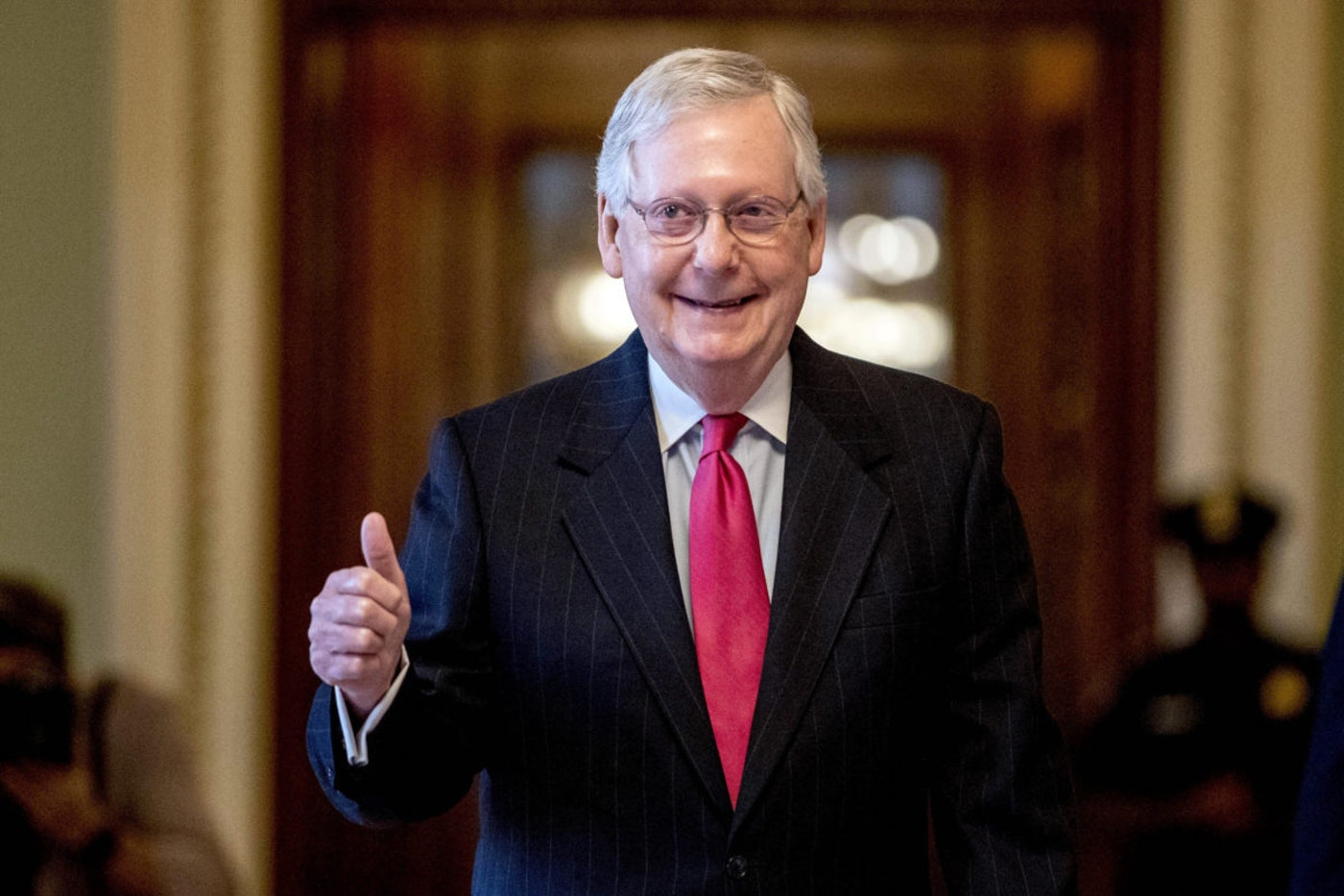 In this March 25, 2020, file photo, Senate Majority Leader Mitch McConnell, R-Ky. gives a thumbs up as he leaves the Senate chamber on Capitol Hill in Washington, where a deal has been reached on a coronavirus bill. Overwhelmed Kentucky and New York officials face a deluge of mail-in votes that are likely to delay results for days in high-profile congressional primaries on Tuesday, June 23. There's a lot of interest in two contests in particular. One involves former Marine combat pilot Amy McGrath's fight for the Democratic nomination to challenge Senate Majority Leader Mitch McConnell. (AP Photo/Andrew Harnik)