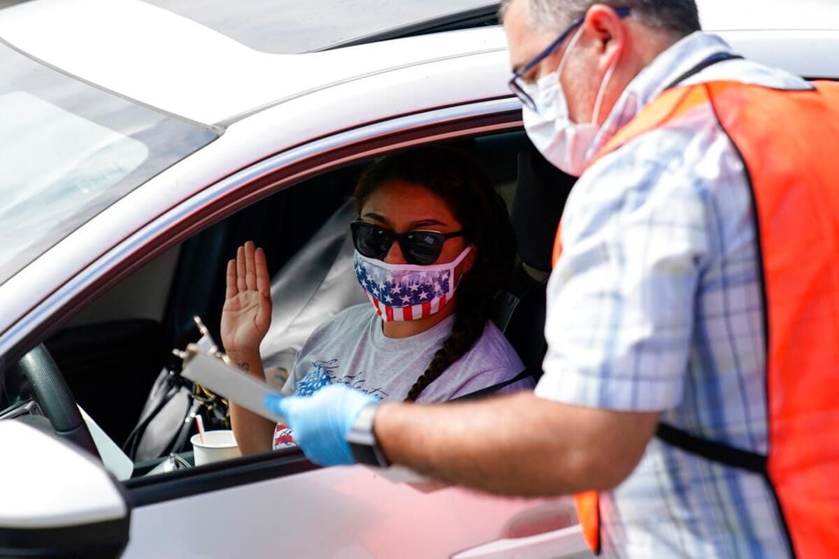 Vida Kazemi is sworn in as a U.S. citizen by Allen Chrysler, immigration services officer, during a drive-up naturalization ceremony. (Image via AP Photo/Ashley Landis)