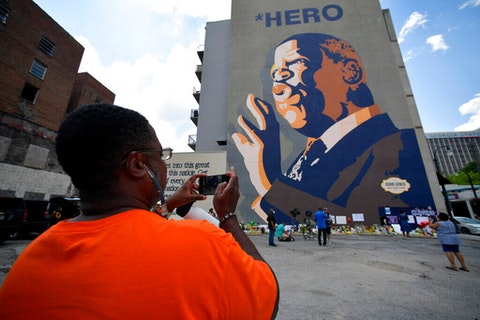 """People gather at a make-shift memorial near the home of Rep. John Lewis, D-Ga., Sunday, July 19, 2020, in Atlanta. Lewis, who died Friday at age 80, was the youngest and last survivor of the Big Six civil rights activists who organized the 1963 March on Washington, and spoke shortly before the group's leader, Rev. Martin Luther King Jr., gave his """"I Have a Dream"""" speech to a vast sea of people. (AP Photo/Mike Stewart)"""