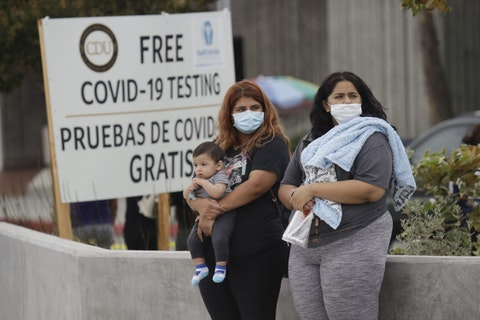 Two women and a child wait to take a Coronavirus test at a mobile testing site at the Charles Drew University of Medicine and Science Wednesday, July 22, 2020, in Los Angeles.  (AP Photo/Marcio Jose Sanchez)