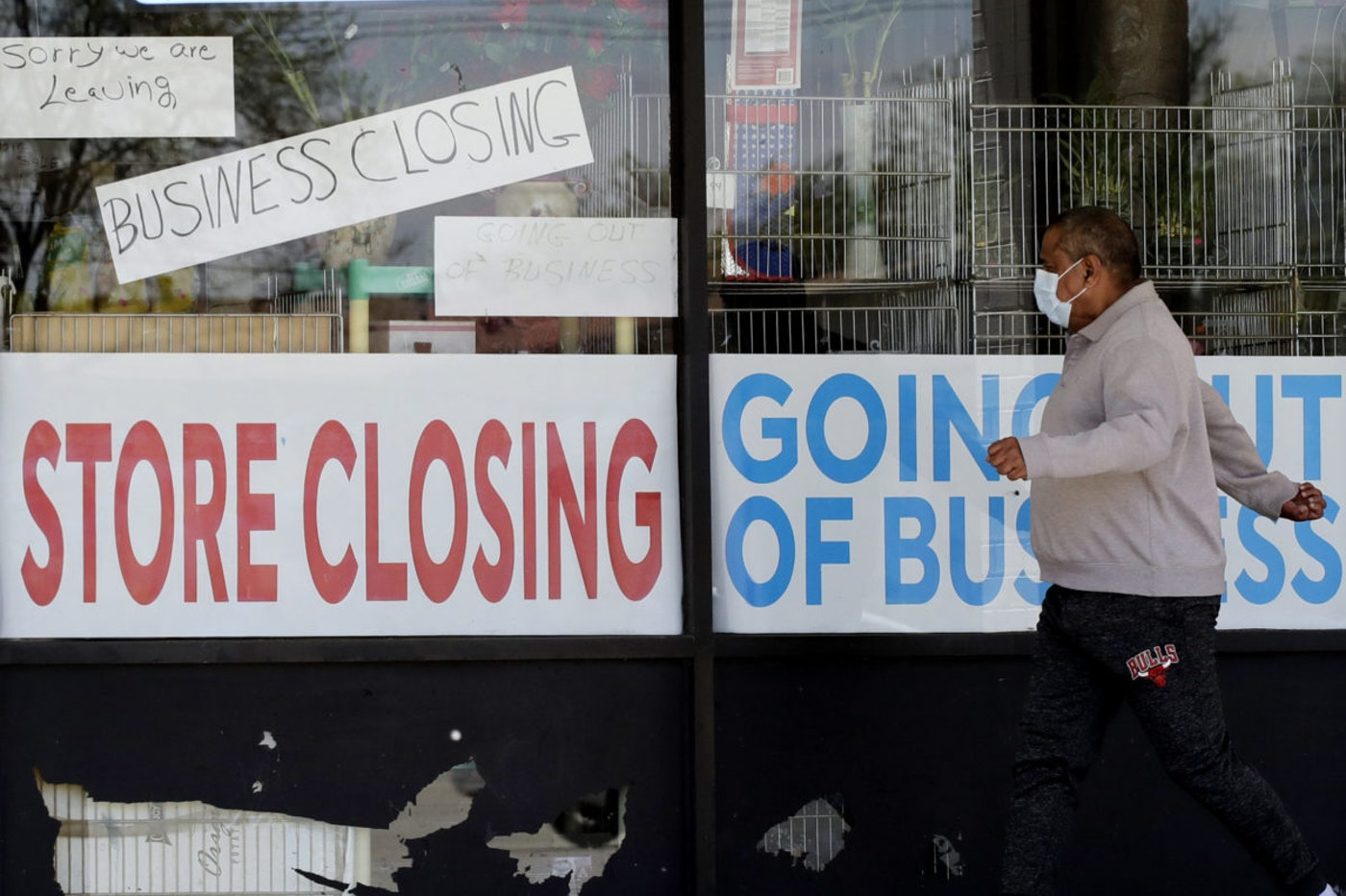 In this May 21, 2020 file photo, a man looks at signs displayed of a store closing due to the coronavirus pandemic in Niles, Ill. The viral pandemic's resurgence caused the number of Americans seeking unemployment benefits to rise last week for the first time in nearly four months, evidence of the deepening economic pain the outbreak is causing. (AP Photo/Nam Y. Huh, File)