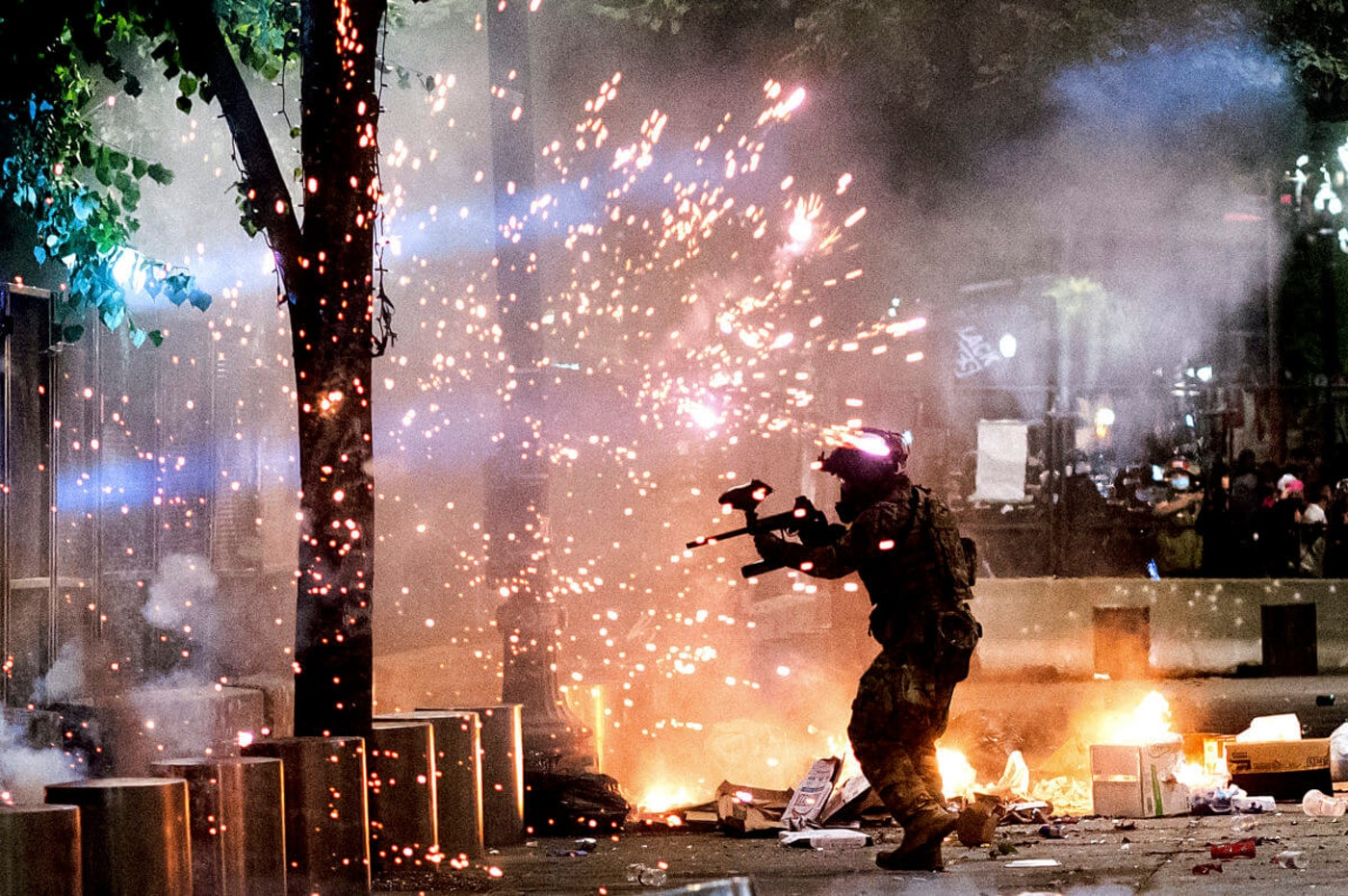 A federal officer fires crowd control munitions at Black Lives Matter protesters at the Mark O. Hatfield United States Courthouse on Friday, July 24, 2020, in Portland, Ore. Since federal officers arrived in downtown Portland in early July, violent protests have largely been limited to a two block radius from the courthouse. (AP Photo/Noah Berger)