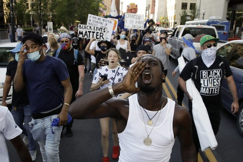 In this June 20, 2020, file photo, demonstrators march near the BOK Center in Tulsa, Okla. (AP Photo/Charlie Riedel, File)