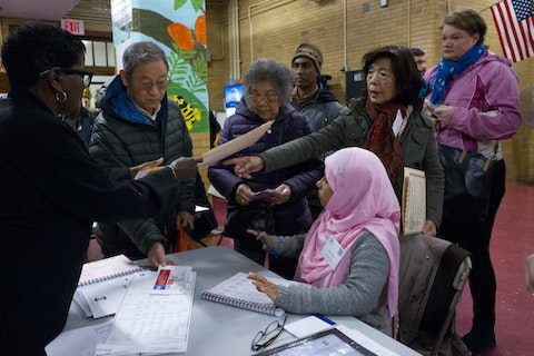 Poll worker Amirun Nessa, seated right, assists voters in Brooklyn, NY. (AP Photo/Mark Lennihan)