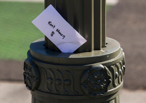"""A paper envelope written with the words """"Rent Money $ """" is left tucked in a lighting pole in the Boyle Heights east district of the city of Los Angeles on Wednesday, April 1, 2020. (AP Photo/Damian Dovarganes)"""