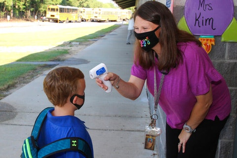 In a photo provided by Newton County Schools, teaching assistant Crystal May talks to kindergarten student Lewis Henry Thompson, 5, as she takes his temperature at Newton County Elementary School in Decatur, Miss., Monday, Aug. 3, 2020. Thousands of students across the nation resumed in-person school Monday for the first time since March. Parents are having to balance the children's need for socialization and instruction that school provides, with the reality that the U.S. death toll from the coronavirus has hit about 155,000 and cases are rising in numerous places. (Janine Vincent/Newton County Schools via AP)