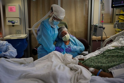 Romelia Navarro, right, is comforted by nurse Michele Younkin as she weeps while sitting at the bedside of her dying husband, Antonio, in St. Jude Medical Center's COVID-19 unit in Fullerton, Calif. (AP Photo/Jae C. Hong)