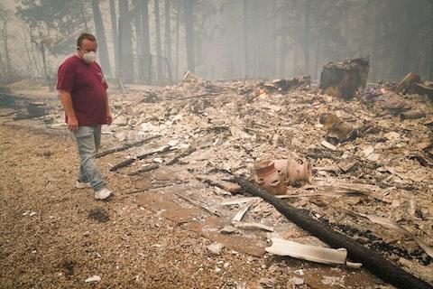 Peter Koleckar walks around a burned down home in his neighborhood after the CZU August Lightning Complex Fire passed through on Thursday, Aug. 20, 2020, in Bonny Doon, Calif. The fire spared Koleckar's home. (AP Photo/Marcio Jose Sanchez)