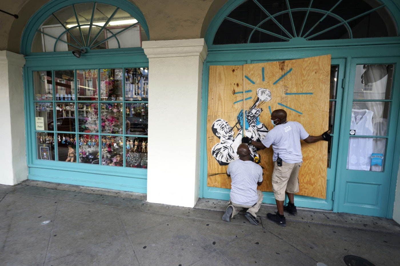 Workers board up shops in the French Quarter of New Orleans, Sunday, Aug. 23, 2020, in advance of storms expected to make landfall on the Southern Louisiana coast. (AP Photo/Gerald Herbert)