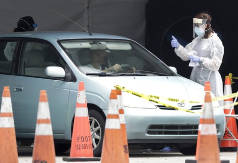 A healthcare worker gives a thumbs up to a driver as he stops his car, Wednesday, Aug. 5, 2020, at a COVID-19 testing site outside Hard Rock Stadium in Miami Gardens, Fla. (AP Photo/Wilfredo Lee)