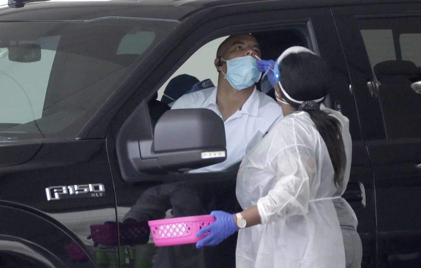 A healthcare worker performs an antigen test, Wednesday, Aug. 5, 2020, at a COVID-19 testing site outside Hard Rock Stadium in Miami Gardens, Fla. State officials say Florida has surpassed 500,000 coronavirus cases. (AP Photo/Wilfredo Lee)
