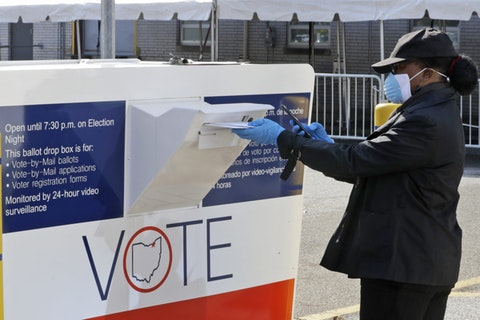 Marcia McCoy drops her ballot into a box outside the Cuyahoga County Board of Elections, Tuesday, April 28, 2020, in Cleveland, Ohio. (AP Photo/Tony Dejak)