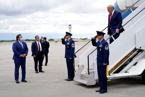 President Donald Trump walks to greet Florida Gov. Ron DeSantis as he arrives at West Palm Beach International Airport, Tuesday, Sept. 8, 2020, in West Palm Beach, Fla. (AP Photo/Evan Vucci)