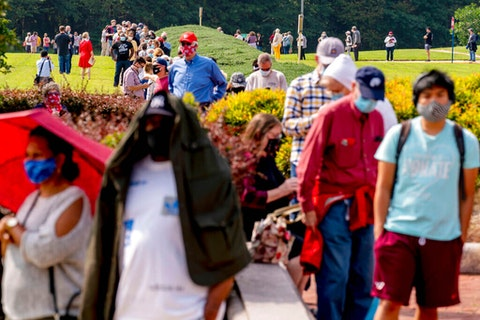 A line stretching the equivalent of two football fields forms as hundreds wait in line for early voting at Fairfax County Government Center, Friday, Sept. 18, 2020, in Fairfax, Va. (AP Photo/Andrew Harnik)