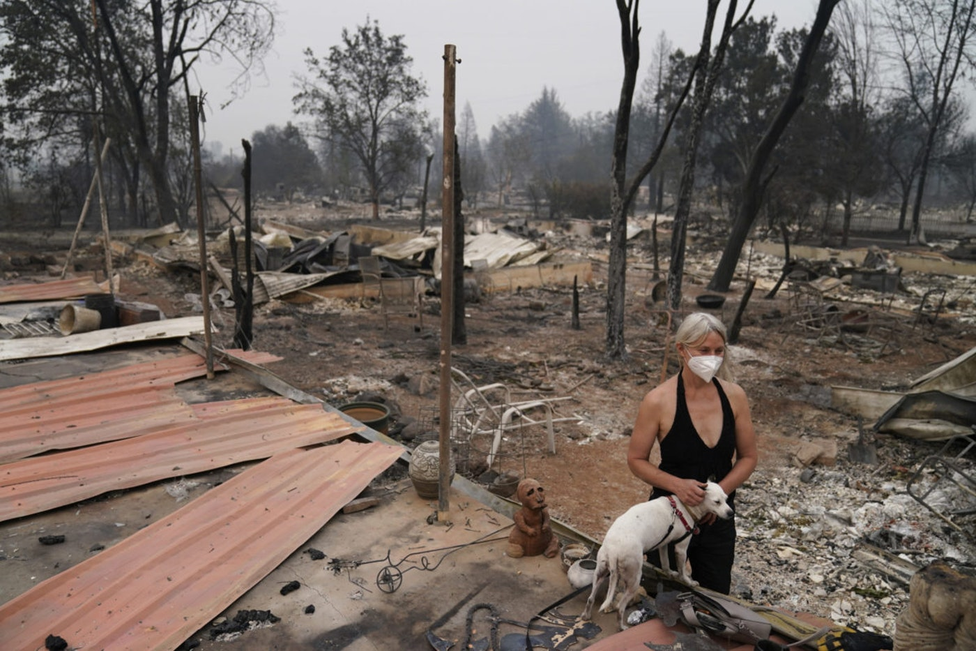 Eden McCarthy pets her dog Hina in the rubble of her home destroyed by the Almeda Fire, Thursday, Sept. 10, 2020, in Talent, Ore. (AP Photo/John Locher)
