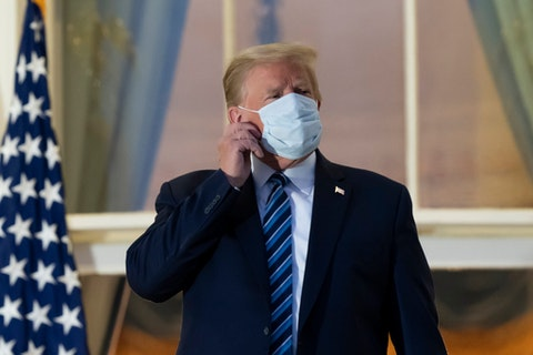 President Donald Trump removes his mask as he stands on the Blue Room Balcony upon returning to the White House after leaving Walter Reed National Military Medical Center. Trump announced he tested positive for COVID-19 on Oct. 2.