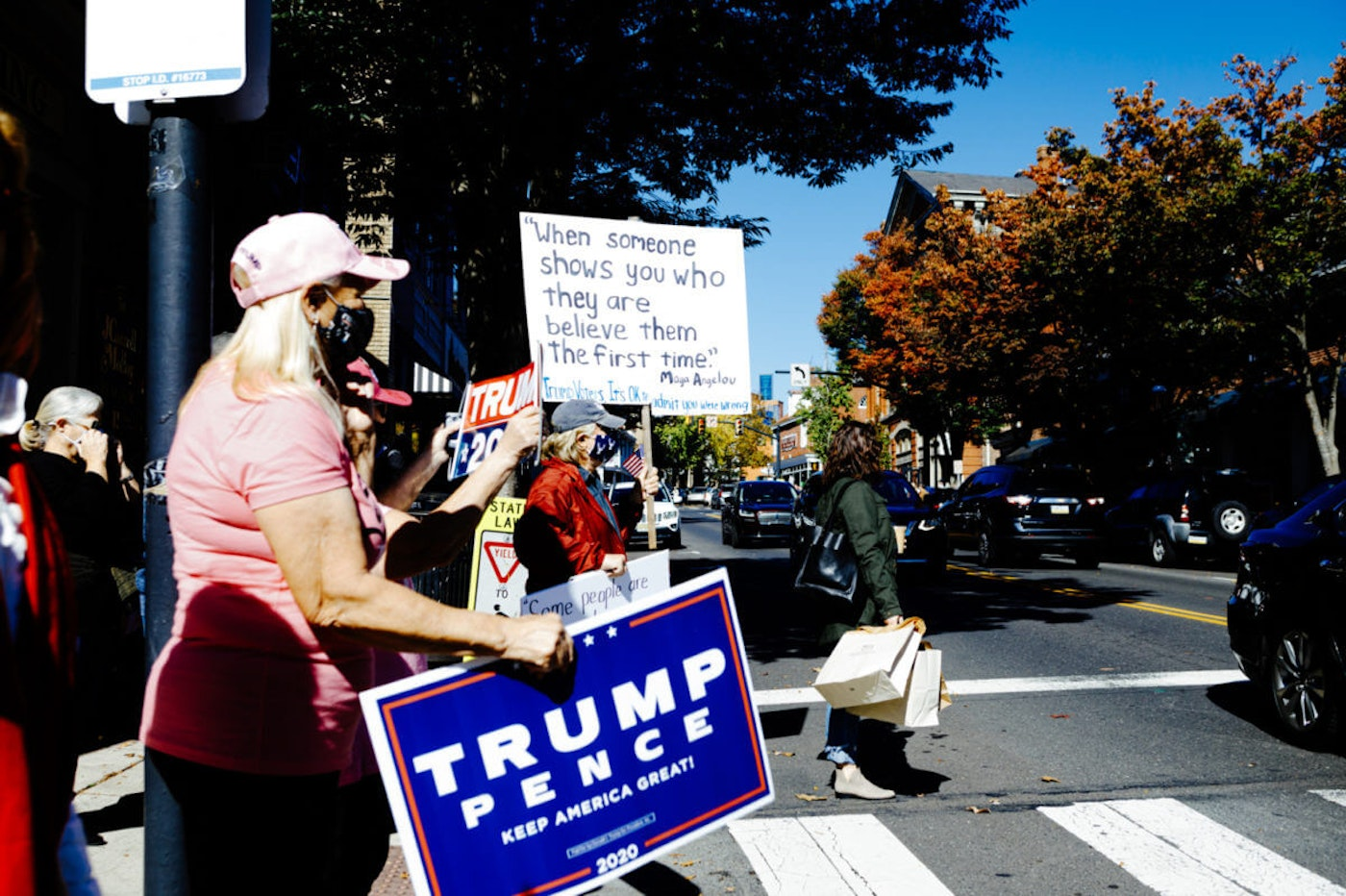 "Joe Biden supporters, including a woman carrying a sign telling Donald Trump supporters ""it's OK to admit you were wrong,"" and Trump supporters meet on Oct. 17, 2020, in downtown Doylestown, Bucks County. The two groups had gathered in the center of town to greet or protest a vehicle parade of Trump supporters. (Photo courtesy of Mike Maney)"