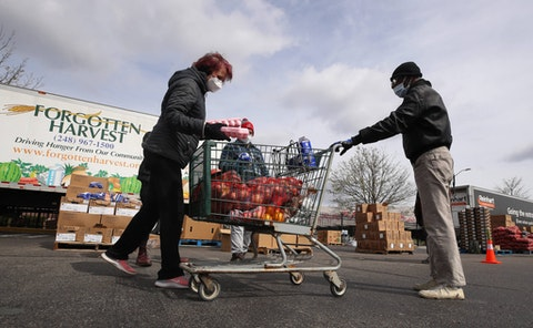DETROIT, MICHIGAN - APRIL 14: A volunteer with Forgotten Harvest loads food into a cart at a mobile pantry April 14, 2020 in Detroit, Michigan. The organization distributes food throughout the metro area, which has seen an uptick in demand due to the COVID-19 pandemic. (Photo by Gregory Shamus/Getty Images)