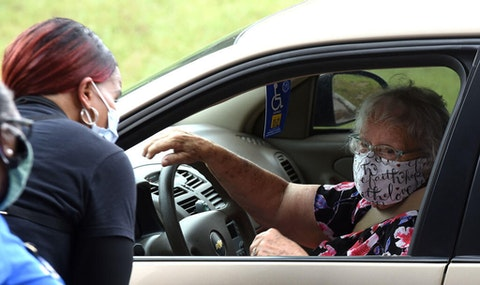 Volunteers speak with a woman while boxes of food for the needy from the Second Harvest Food Bank of Central Florida are being packed in her car during a drive through event at City of Destiny church.  The demand for food continues in the Orlando, Florida area due to the large numbers of service workers and others who have become unemployed due to the coronavirus pandemic. (Photo by Paul Hennessy/SOPA Images/LightRocket via Getty Images)