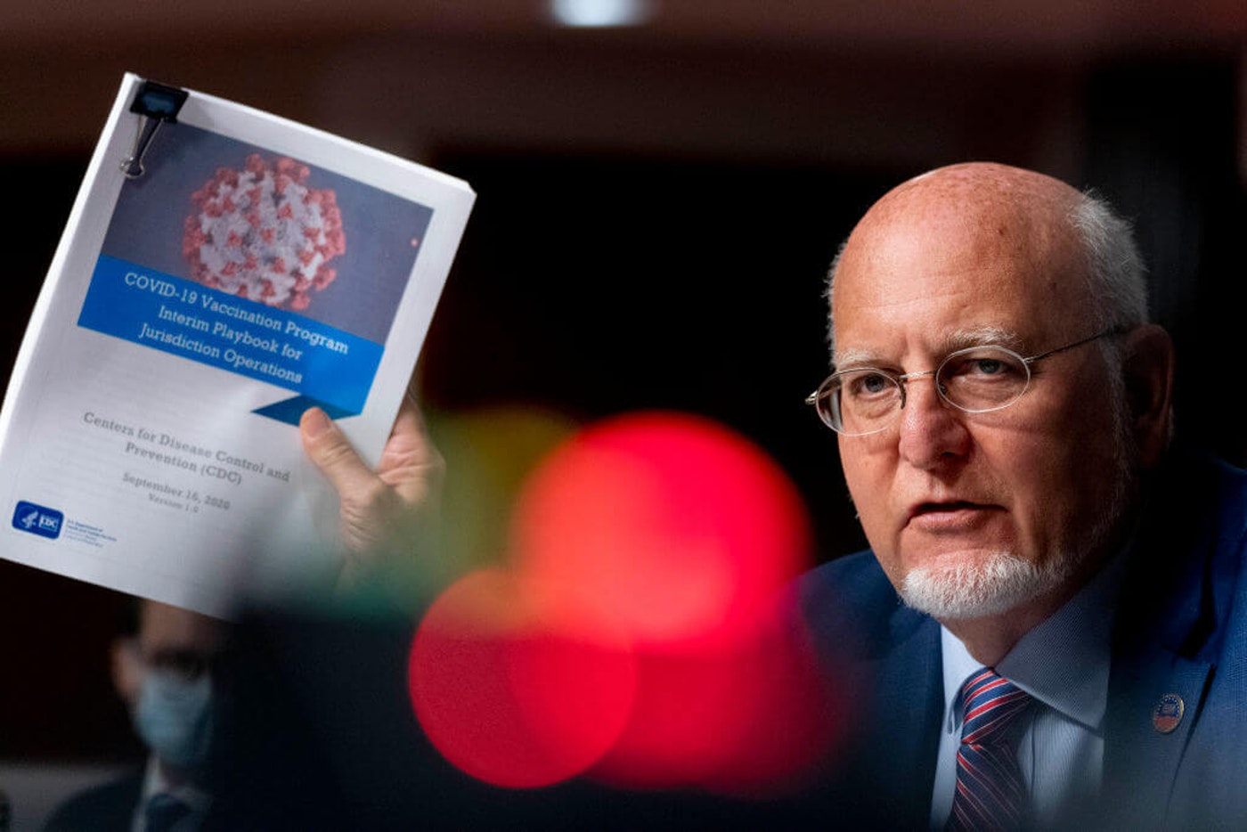 Centers for Disease Control and Prevention (CDC) Director Dr. Robert Redfield holds up a CDC document while he speaks at a hearing of the Senate Appropriations subcommittee reviewing coronavirus response efforts on September 16, 2020 in Washington, DC.  (Photo by Andrew Harnik-Pool/Getty Images)