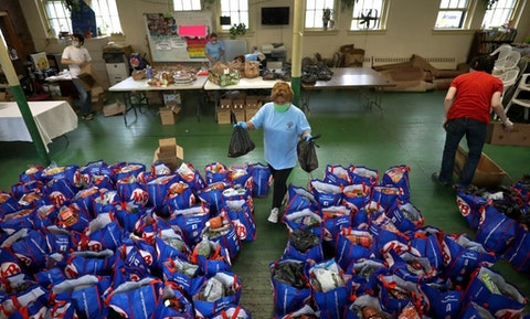 Paulina Bastidas-Yale, an unemployed downtown office cleaner, helps distribute food at the Our Savior Lutheran Church on Paris St. in East Boston on Sept. 22, 2020. Bastidas was left unemployed after office workers left Boston to work from home during the COVID-19 pandemic. (Photo by David L. Ryan/The Boston Globe via Getty Images)