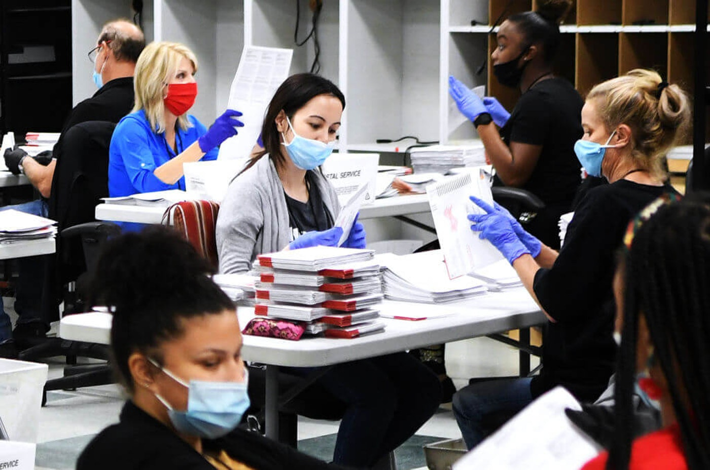 Election office workers wear face masks and gloves as they process mail-in ballots in the ballot duplicating room at the Orange County Supervisor of Elections office on October 26, 2020 in Orlando, Florida. With nine days until the November 3 election, more people already have cast ballots in this years presidential election than voted early or absentee in the 2016 race.  (Photo by Paul Hennessy/NurPhoto via Getty Images)