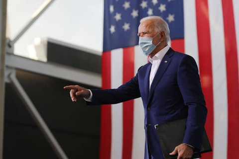 Wearing a face mask to reduce the risk posed by the coronavirus, Democratic presidential nominee Joe Biden points to supporters during a drive-in voter mobilization event at Miramar Regional Park October 13, 2020 in Miramar, Florida. With three weeks until Election Day, Biden is campaigning in Florida. (Photo by Chip Somodevilla/Getty Images)