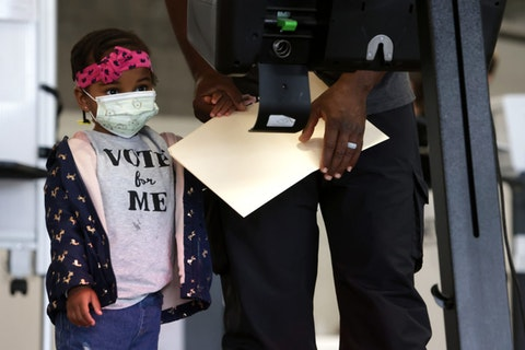Two-year-old Aissatou Barry accompanies her father to vote at an early voting center at Union Market October 27, 2020 in Washington, DC. (Photo by Alex Wong/Getty Images)