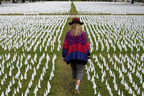 In this Oct. 27, 2020, Artist Suzanne Brennan Firstenberg walks among thousands of white flags planted in remembrance of Americans who have died of COVID-19 near Robert F. Kennedy Memorial Stadium in Washington. (AP Photo/Patrick Semansky, File)